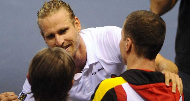 Peter Gojowczyk celebrates with his team-mates after stunning victory