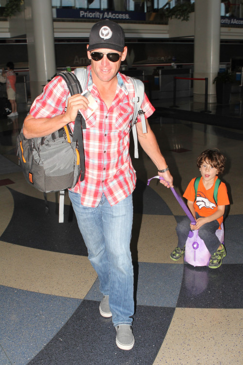 Lance Armstrong carts his son Max on a suitcase before a flight at LAX